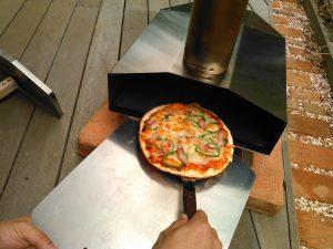 焼き上がったピザを取り出す