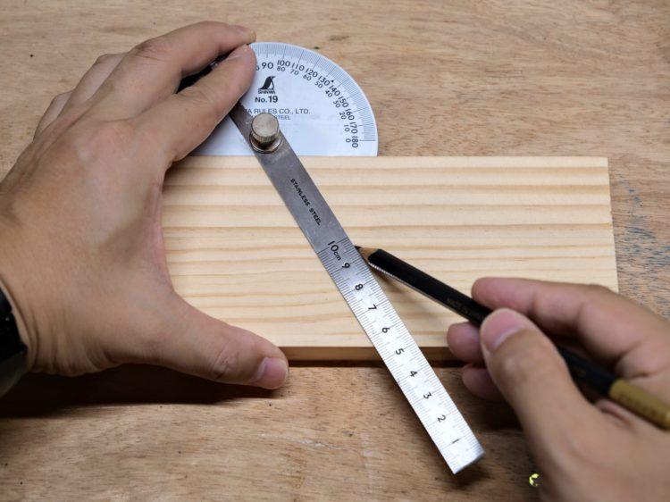 分度板を部材に押し当て墨線を引く
